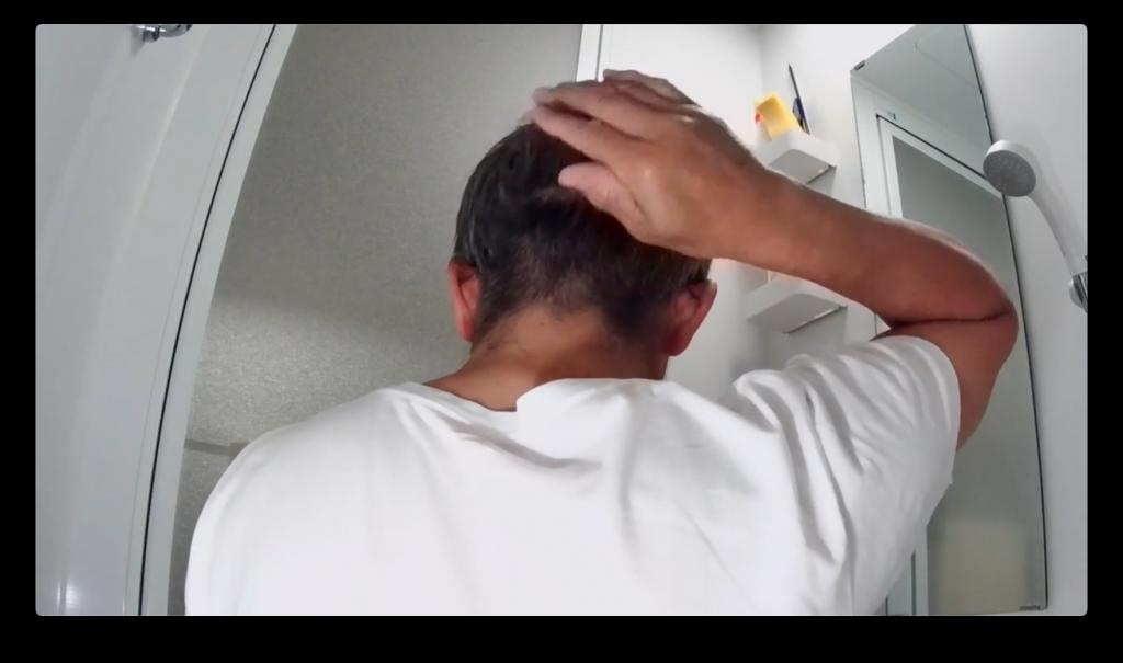 手ですいて後頭部の髪の毛の長さを確認